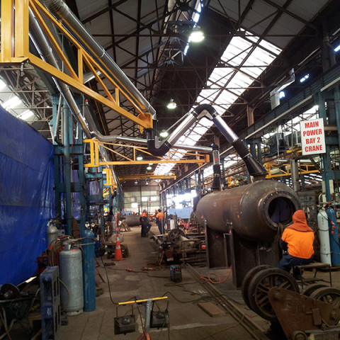 Large heavy fabrication shop fitted with centralised extraction system with 4m extension booms with 3m extraction arms. Tenix NZ.
