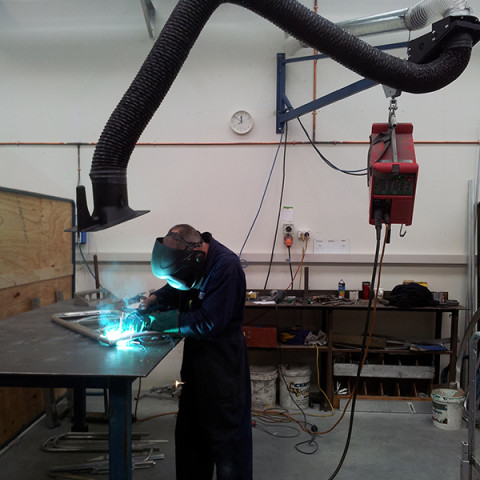 Typical welding bay with wire feeder mounted on boom and Armoflex arm.